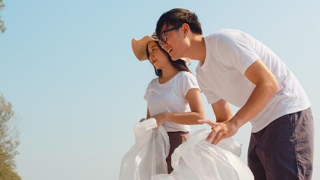 Ativistas felizes novos asiáticos da família que recolhem resíduos plásticos na praia. os voluntários da ásia ajudam a manter a natureza limpa e a recolher o lixo. conceito sobre problemas de poluição de conservação ambiental. Foto gratuita