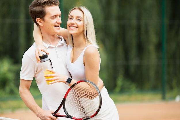 Ativo homem e mulher na quadra de tênis Foto gratuita