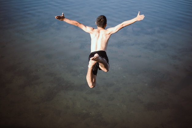 Ativo menino pulando na água Foto gratuita