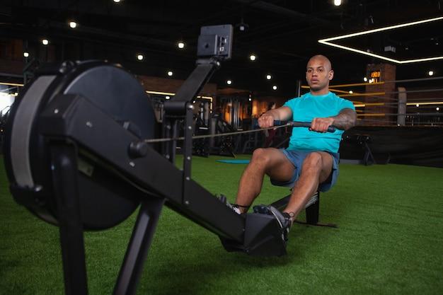 Atleta africano masculino bonito malhando na academia Foto Premium