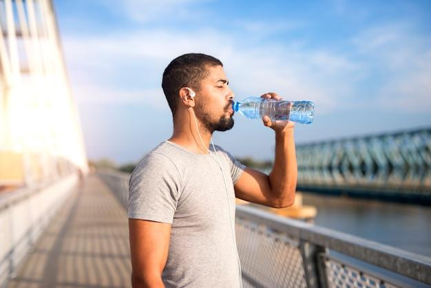 Atleta atraente bebendo água após um treino intenso Foto gratuita