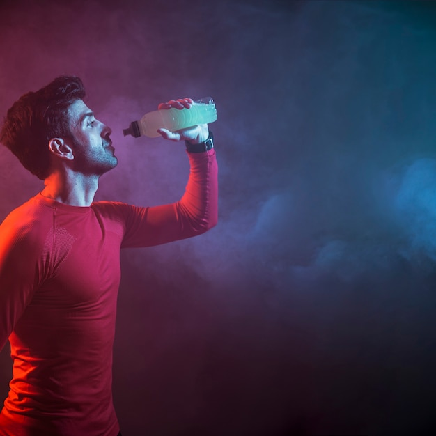 Atleta bebendo água no escuro Foto Premium