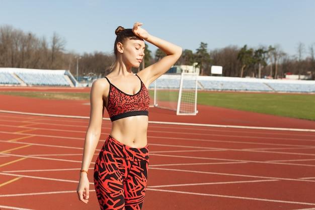 Atleta caucasiano linda garota descansando depois de correr em uma pista de corrida. Foto Premium