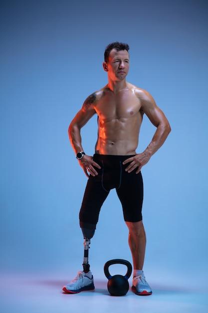 Atleta com deficiência ou amputado isolado no fundo azul do estúdio. esportista profissional masculino com treinamento de prótese de perna com pesos em neon. Foto gratuita