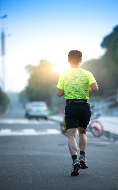 Atleta de corredor correndo na estrada. mulher aptidão sunrise movimentando-se treino bem-estar conceito. Foto Premium