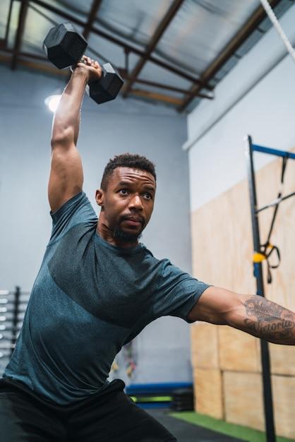Atleta de crossfit fazendo exercício com halteres. Foto Premium