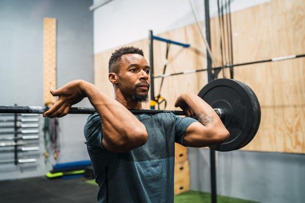 Atleta de crossfit fazendo exercício com um barbell. Foto gratuita