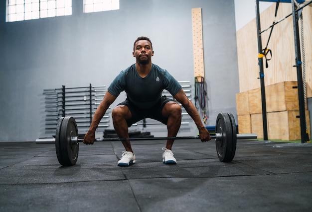 Atleta de crossfit fazendo exercício com uma barra. Foto gratuita