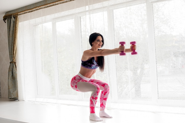 Atleta de fitness sensual realiza exercícios nas nádegas no estúdio. musculação. Foto Premium