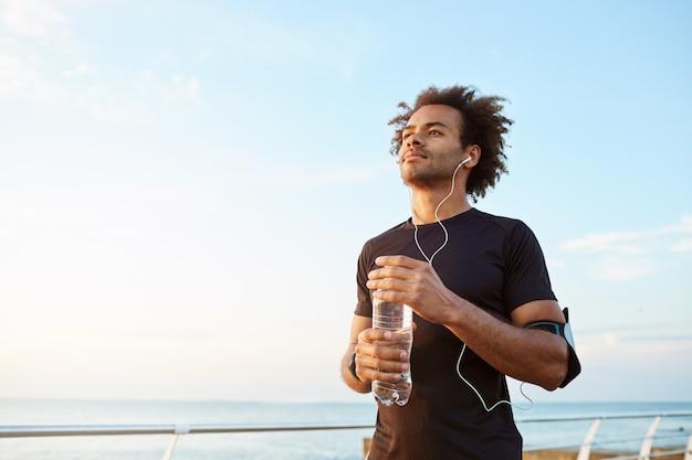 Atleta de homem bebendo água de uma garrafa de plástico após um treino de corrida difícil. esportista de pele escura olhando para o céu enquanto corre, apreciando a vista Foto gratuita