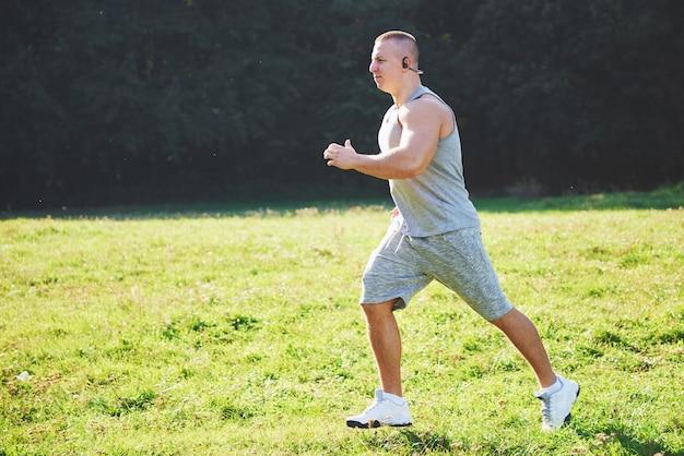 Atleta de homem fitness correndo na natureza durante o pôr do sol. Foto gratuita