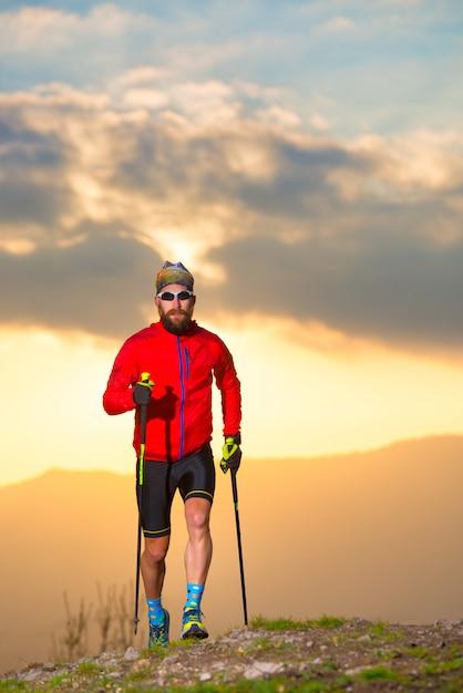Atleta de homem praticando trilha com paus na imagem vertical do sol Foto Premium