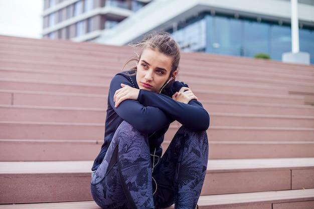 Atleta de mulher sentada na escada enquanto ouve música durante o exercício de jogging Foto Premium