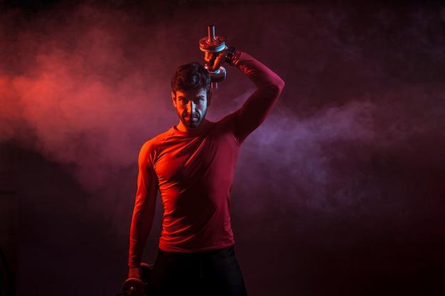 Atleta determinado com dumbbells no escuro Foto gratuita
