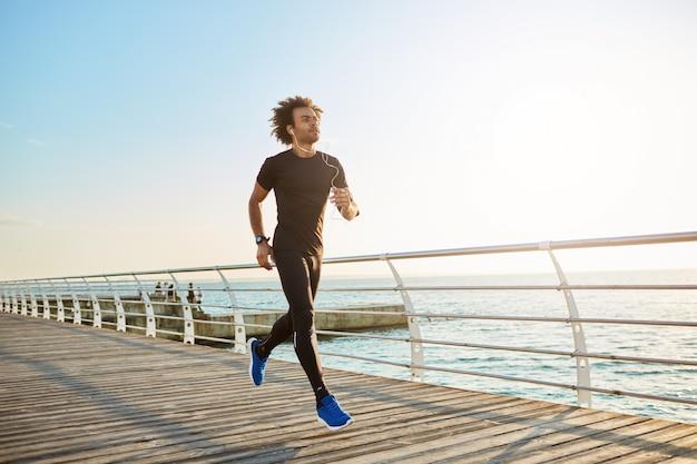 Atleta do sexo masculino atraente vestindo roupas esportivas pretas elegantes e tênis azuis. figura de atleta homem fazendo exercícios aeróbicos em uma manhã ensolarada de verão. Foto gratuita
