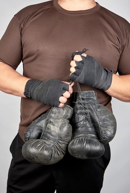 Atleta em roupas marrons detém luvas de boxe pretas de couro vintage muito antigo Foto Premium