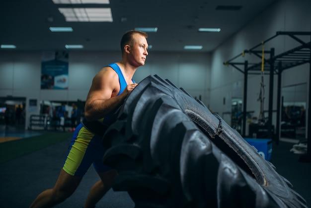 Atleta fazendo exercícios com pneu de caminhão, crossfit Foto Premium