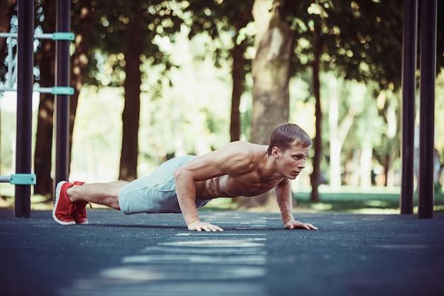Atleta fazendo exercícios no estádio no parque Foto gratuita