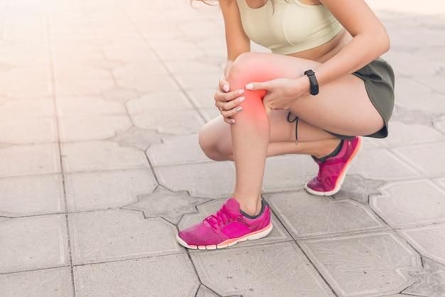 Atleta feminina, agachando-se na calçada com dores no joelho Foto Premium