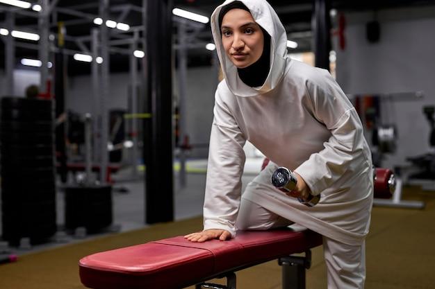 Atleta feminina em treinamento de hijab com halteres no moderno centro de fitness, jovem muçulmana está cheia de energia e poder. motivação, estilo de vida saudável e conceito de esporte Foto Premium