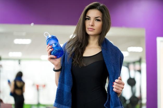 Atleta feminina segurando uma garrafa de água com uma toalha em volta do pescoço Foto Premium