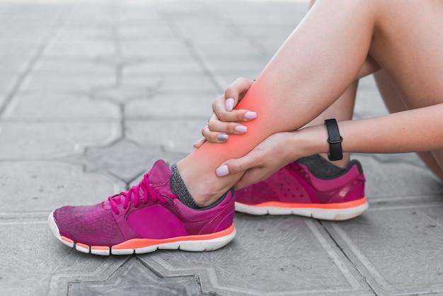 Atleta feminina tendo lesão no tornozelo sentado na calçada Foto gratuita