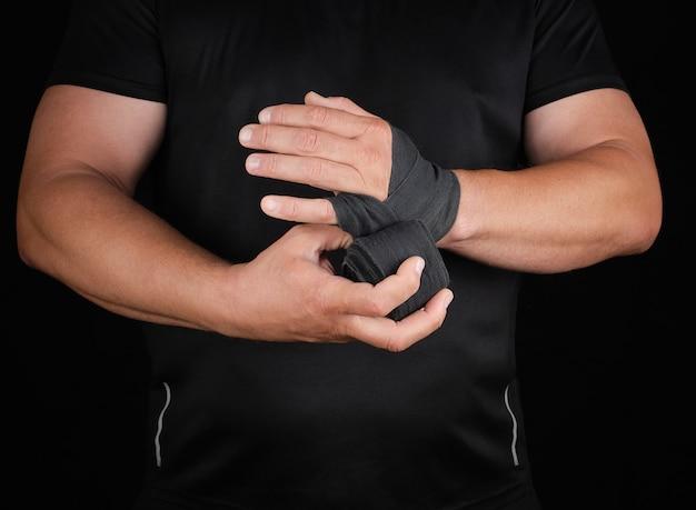 Atleta fica em roupas pretas e envolve as mãos em bandagem elástica têxtil Foto Premium