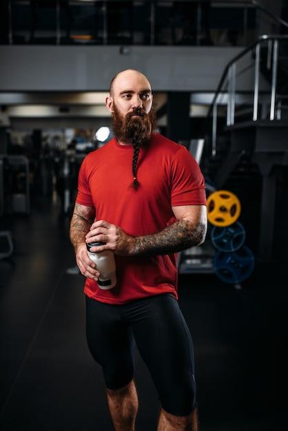 Atleta forte bebe água, treino na academia Foto Premium