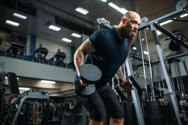 Atleta forte com halteres, treinando na academia Foto Premium