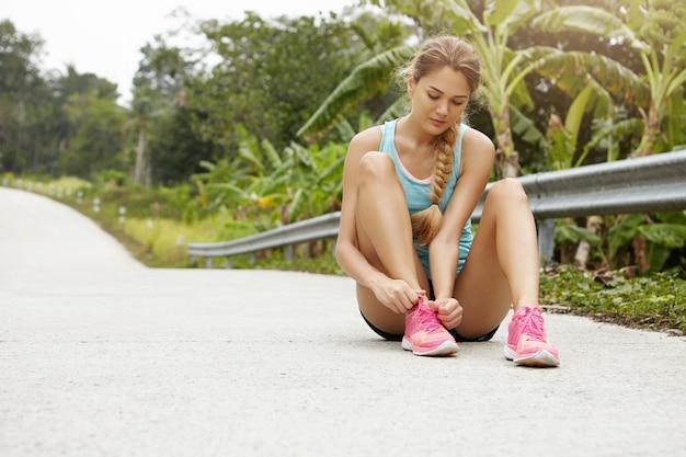 Atleta jovem loira linda em roupas esportivas e tênis rosa amarrando cadarços enquanto fazia uma pausa durante o treino de corrida, sentada na estrada contra uma floresta verde com árvores tropicais Foto gratuita