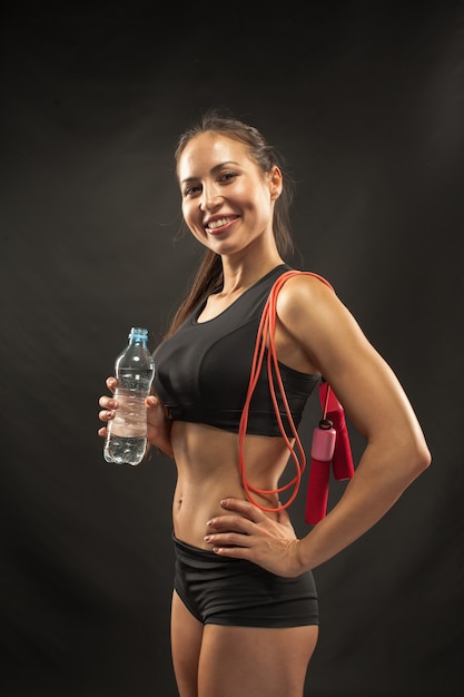 Atleta jovem muscular com uma corda de pular no preto Foto gratuita