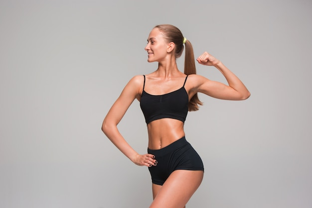 Atleta jovem muscular em cinza Foto gratuita