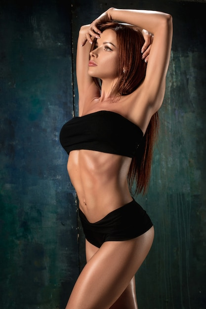 Atleta jovem muscular no preto Foto gratuita