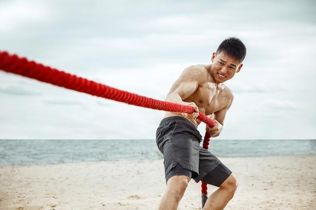 Atleta jovem saudável fazendo agachamentos na praia Foto gratuita