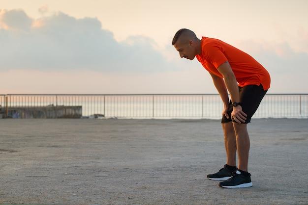 Atleta macho cansado tendo uma ruptura depois de correr Foto gratuita