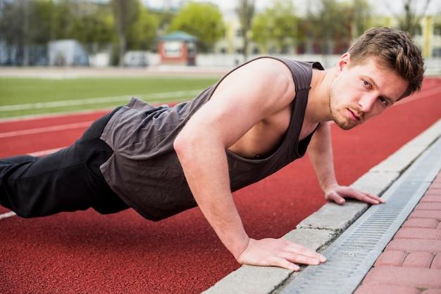 Atleta masculino bonito fazendo flexão na pista de corrida Foto gratuita