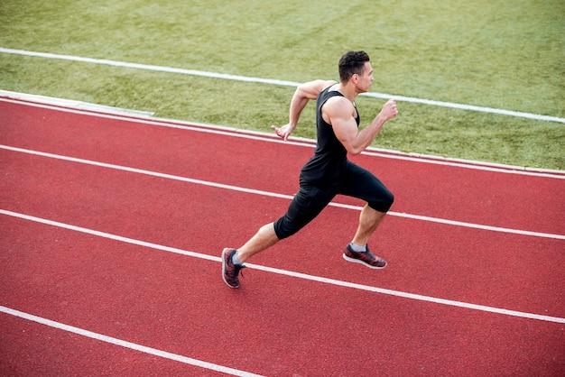 Atleta masculino chega à linha de chegada na pista durante a sessão de treinamento Foto gratuita