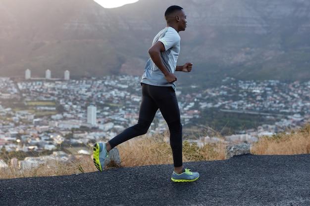 Atleta masculino com corpo esguio e saudável vestido com roupas esportivas, posa de perfil, corre em alta velocidade, participa de maratona, fotografado contra uma bela vista da cidade, cenário de montanhas Foto gratuita