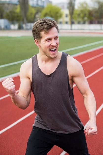 Atleta masculino, comemorando sua vitória na pista de corrida Foto gratuita