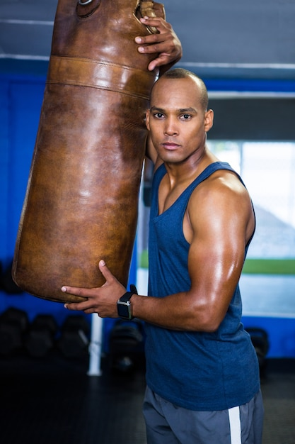 Atleta masculino confiante por saco de pancadas Foto Premium