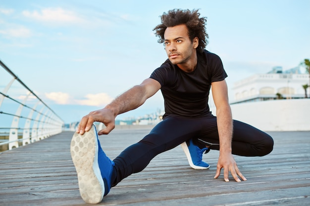 Atleta masculino de pele escura com cabelo espesso, fazendo exercícios e esticando as pernas. Foto gratuita