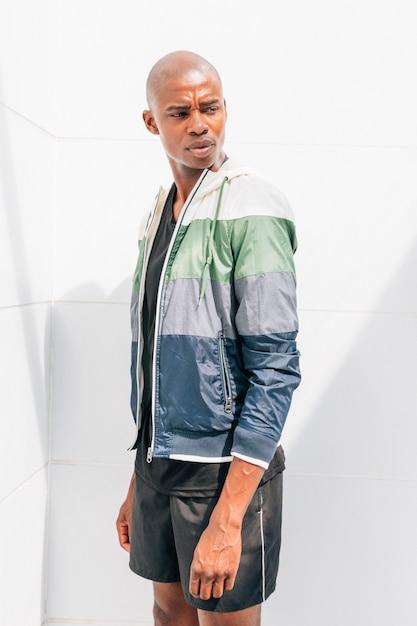 Atleta masculino jovem africano, vestindo jaqueta em pé na frente de parede branca Foto gratuita