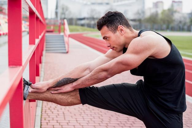 Atleta masculino jovem fitness, esticando a perna no estádio Foto gratuita