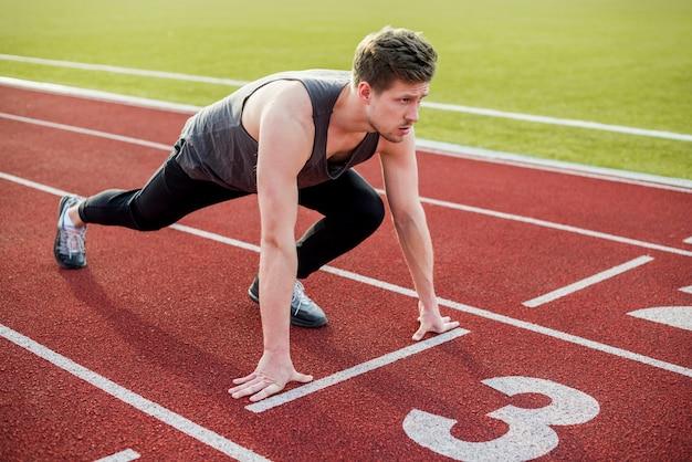 Atleta masculino pronto para começar a corrida na pista de corrida Foto gratuita