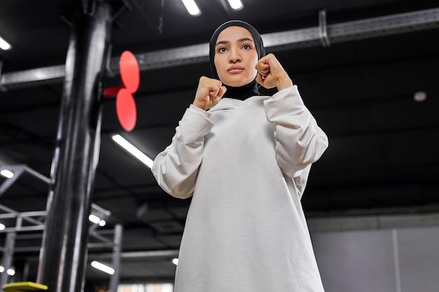 Atleta muçulmana confiante em pose de lutador, indo para bater, envolvida no boxe no centro de fitness, usando um hijab branco. conceito de esporte, treino e fitness Foto Premium