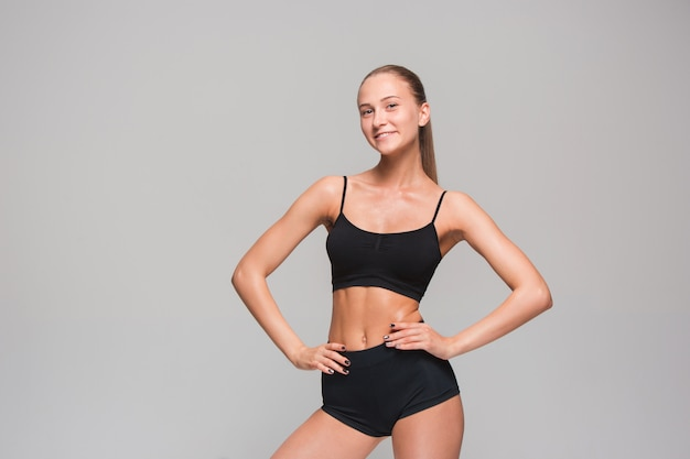 Atleta muscular jovem posando em cinza Foto gratuita