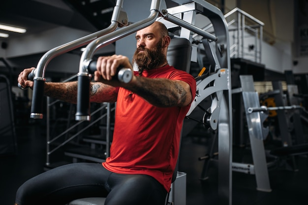Atleta muscular na máquina de exercícios no ginásio. homem barbudo fazendo exercícios no clube esportivo, estilo de vida saudável Foto Premium