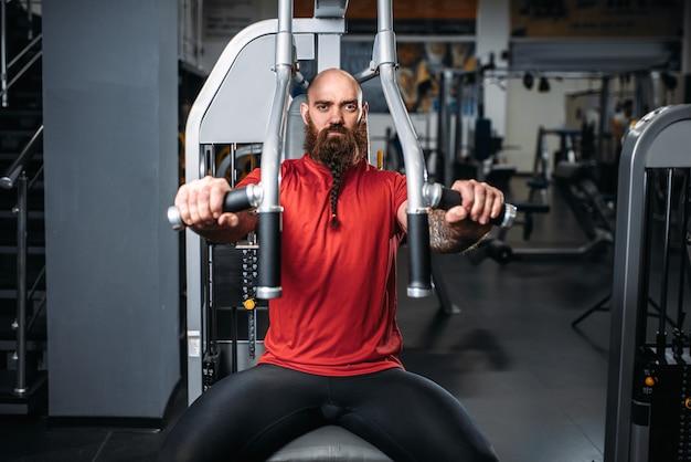 Atleta musculoso na máquina de exercícios na academia Foto Premium