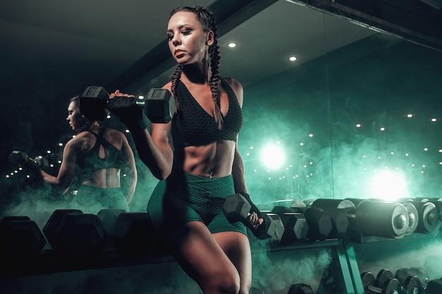 Atleta negra com halteres na academia Foto Premium