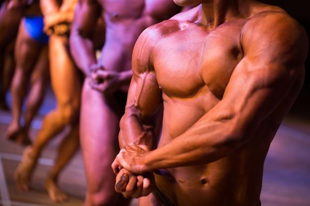 Atletas bodybuilders estão esticando o lado do bíceps do braço Foto Premium